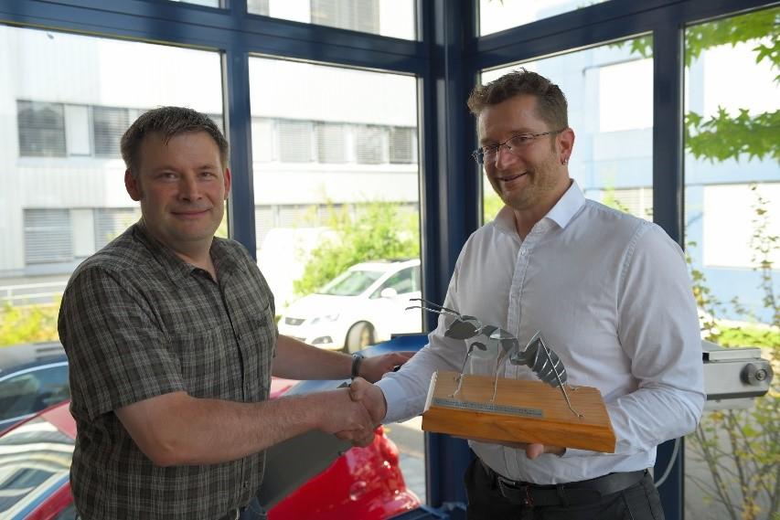 Andreas Stutz (links), Geschäftsführer der Beltrans AG, nimmt das Maskottchen von Blexon als Willkommensgeschenk für den 5000sten Kunden von Bruno Kälin entgegen.